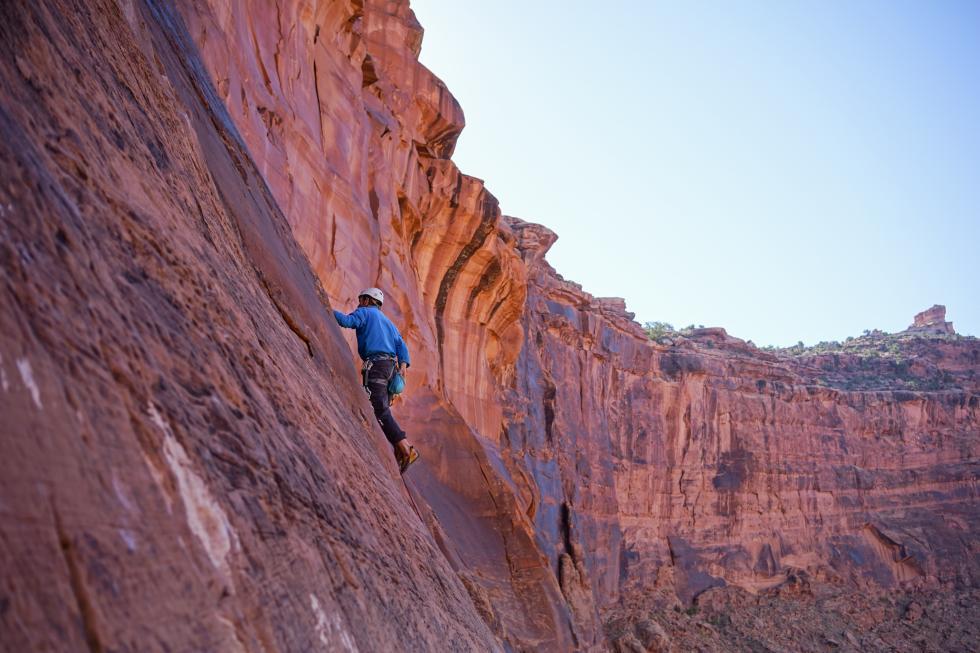 A person rock climbing up a steep mountain.