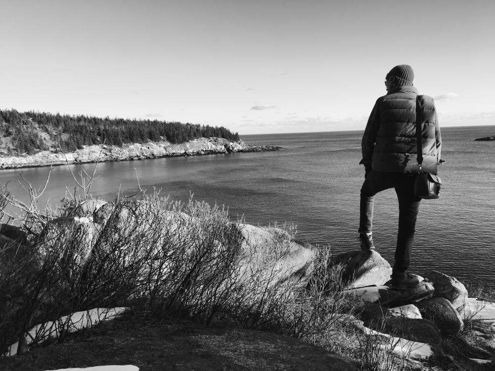 Dan staring out into the ocean at Acadia national park.