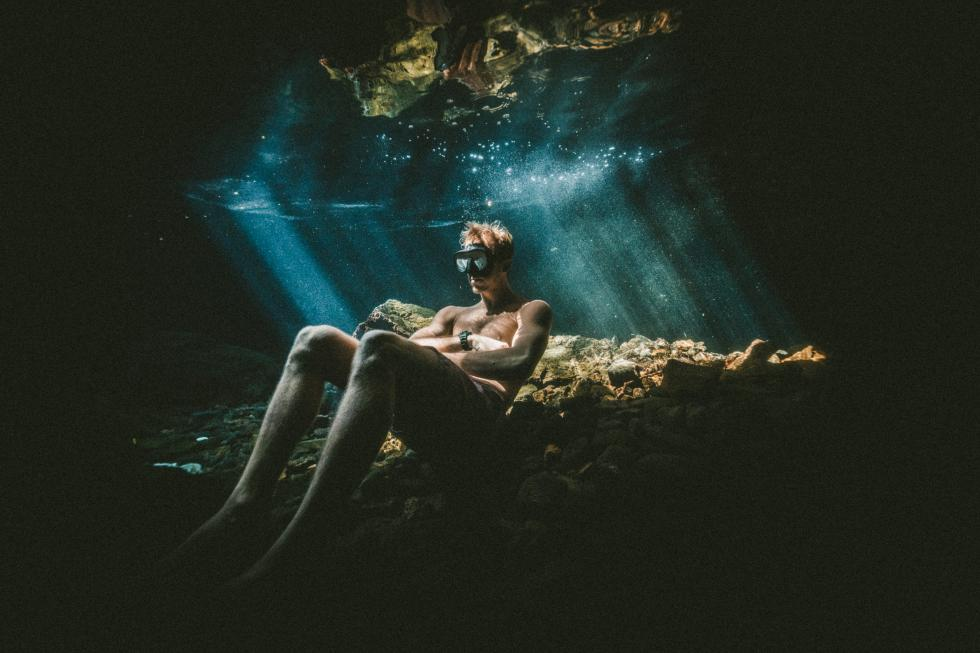 Man underwater sitting peacefully on the bottom.