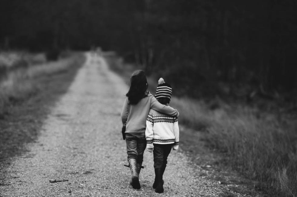 Two kids with arms around each other while walking down a dirt path.