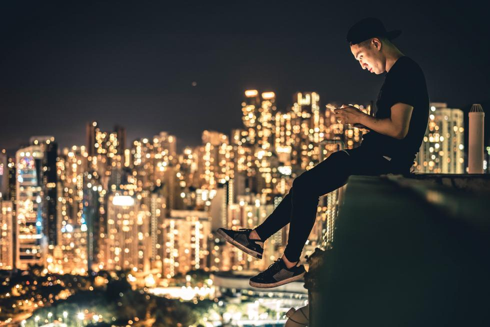 A man on his phone with a backdrop of a city at night.