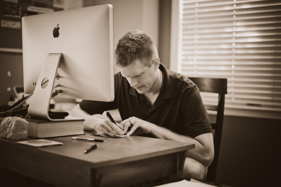 Rick Manelius writing at his desk.
