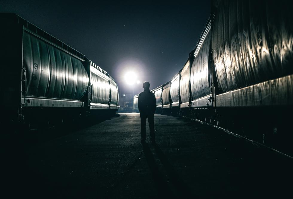 Person standing staring into the dark night sky between two trains.